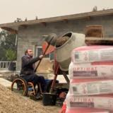 Benoit Fayolle remplit la bétonnière avec le ciment dont la fondation Vicat lui a fait don