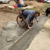 Benoit fayolle en fauteuil nivelle la terrasse en béton de ses mains grâce au don de ciment Vicat