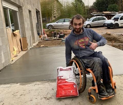 Benoit fayolle en fauteuil devant la terrasse en béton construite de ses mains grâce au don de ciment Vicat