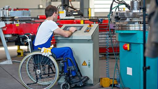 une personne en fauteuil roulant à son poste de travail en usine